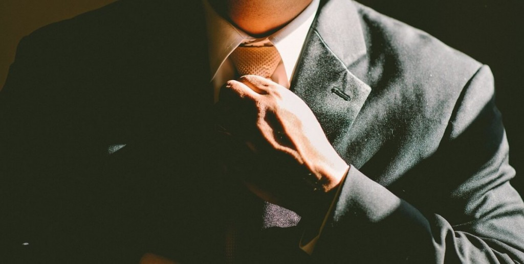 Image of a gentleman in a business suit adjusting his tie